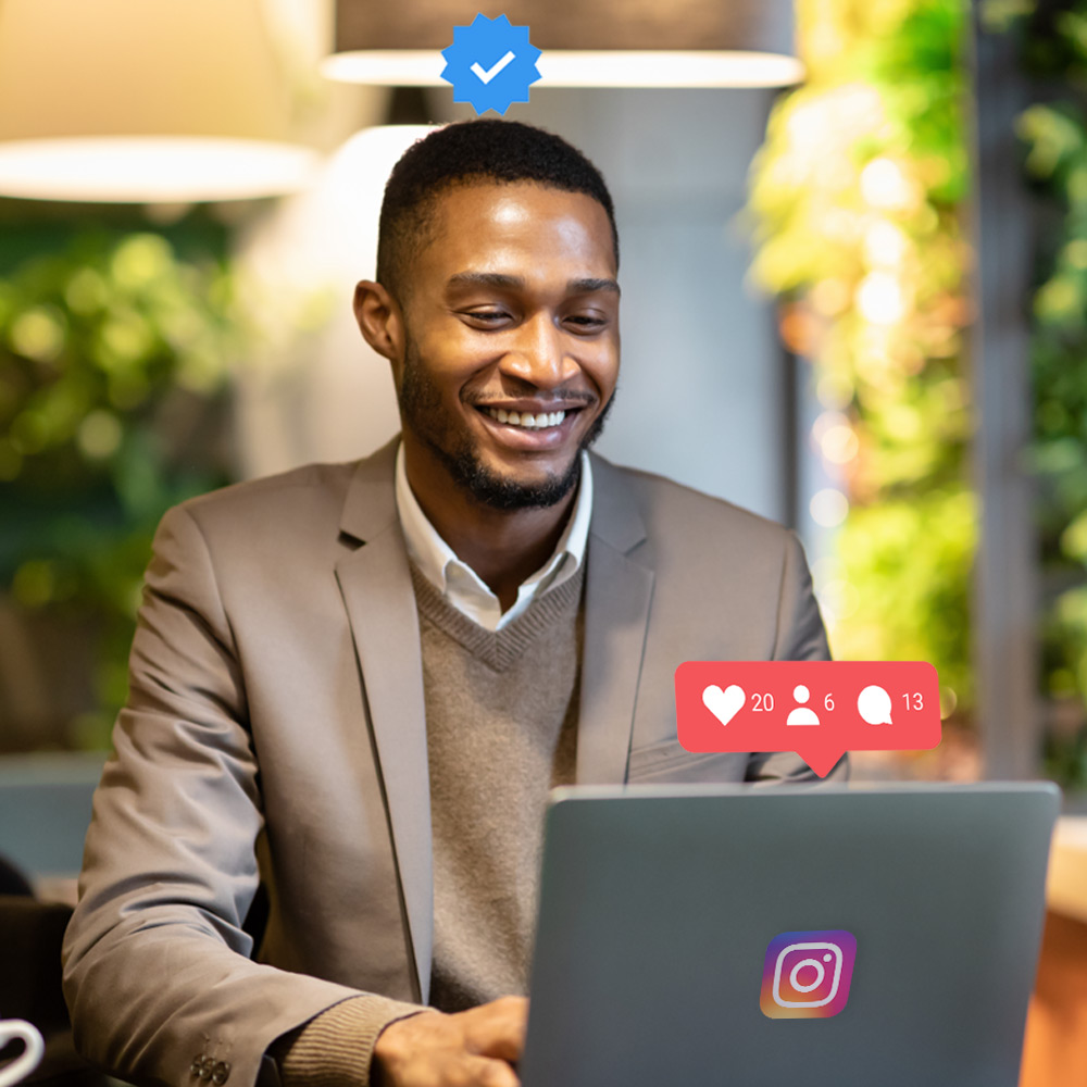 Young Male Adult sitting behind his laptop smiling while he sees his likes, comments and friend requests grow from the help of the instagram algorithm